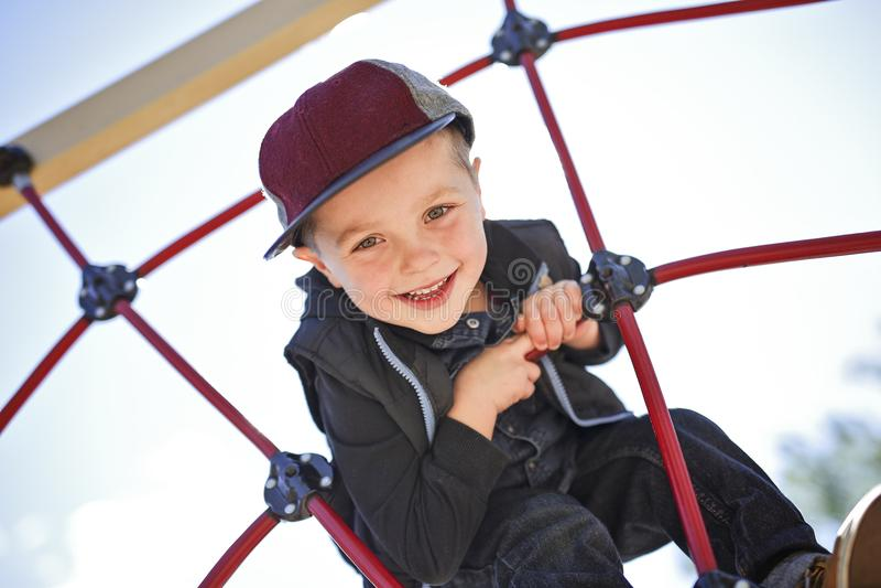 Menino feliz da criança pequena escalado no campo de jogos imagem de stock