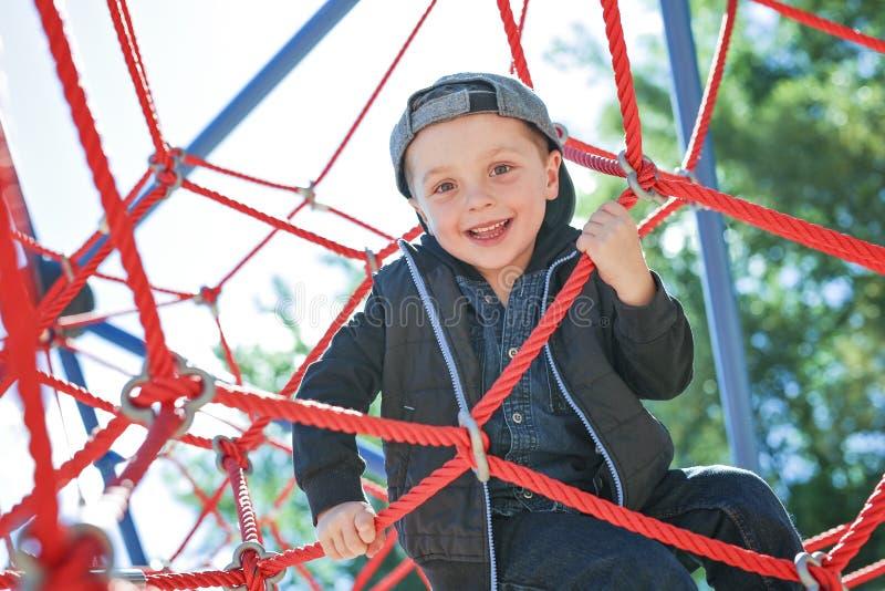 Menino feliz da criança pequena escalado no campo de jogos fotos de stock royalty free