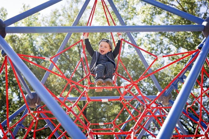 Menino feliz da criança pequena escalado no campo de jogos foto de stock royalty free
