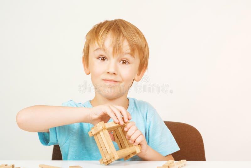 Menino feliz da criança que joga com blocos de madeira e que tem o divertimento Conceito do pensamento lógico Jogos educacionais  fotografia de stock