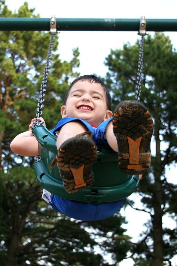 Menino feliz da criança que ri no balanço imagens de stock
