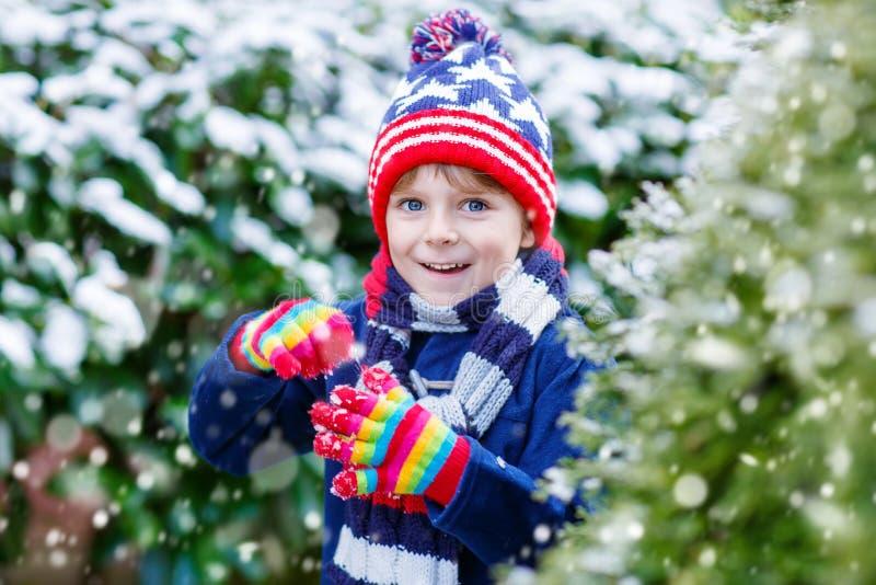 Menino feliz da criança que tem o divertimento com neve no inverno foto de stock royalty free