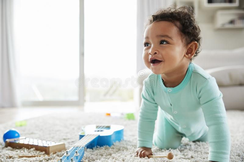 Menino feliz da criança da raça misturada que rasteja na sala de estar fotografia de stock