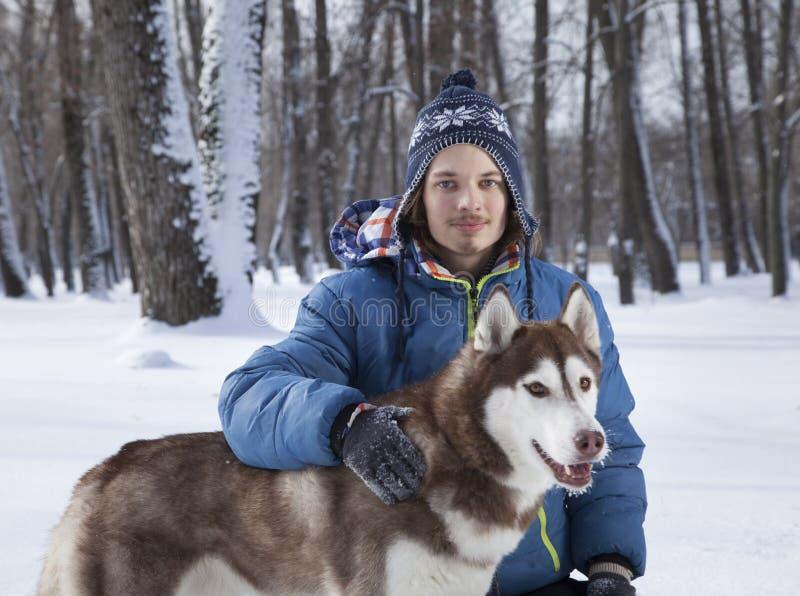 Menino feliz do adolescente do Natal que joga com o cão ronco branco no dia de inverno, o cão e a criança na neve imagem de stock