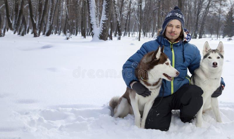 Menino feliz do adolescente que joga com o cão ronco branco no dia de inverno, d imagem de stock royalty free