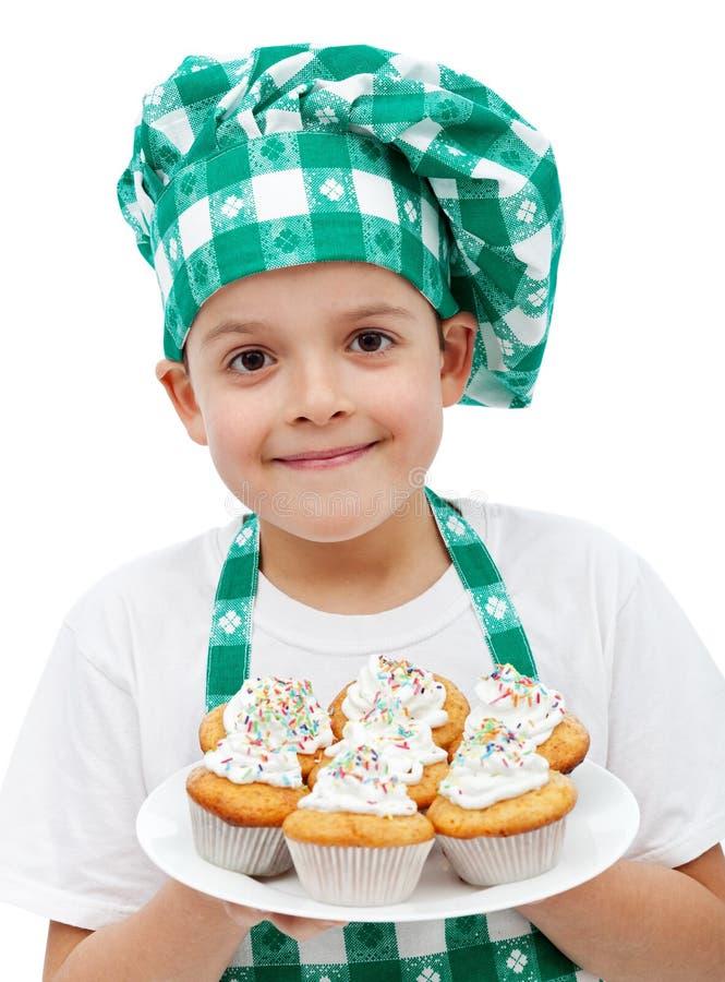 Menino feliz do cozinheiro chefe com uma placa dos queques imagem de stock