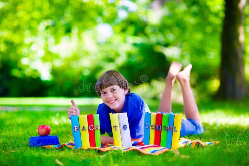 Menino feliz do estudante que relaxa em livros de leitura da jarda de escola foto de stock