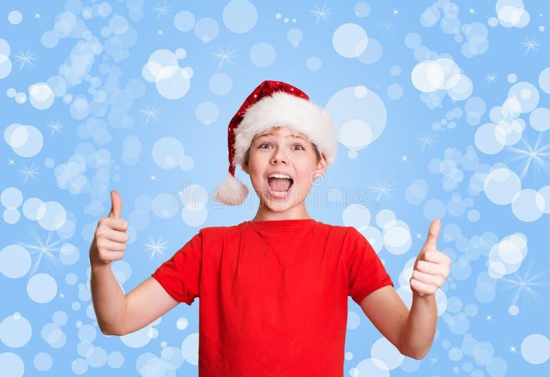 Menino feliz do preteen no chapéu de Santa que faz o polegar acima do gesto no holida fotografia de stock