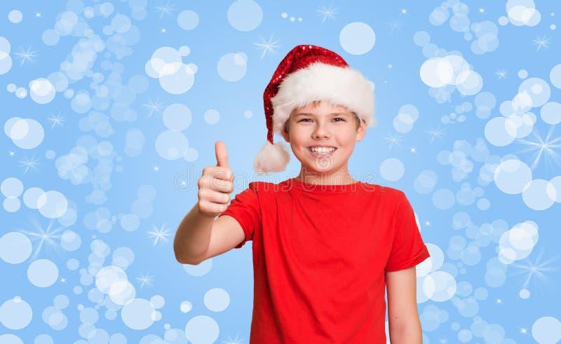 Menino feliz do preteen no chapéu de Santa que faz o polegar acima do gesto no holida fotos de stock