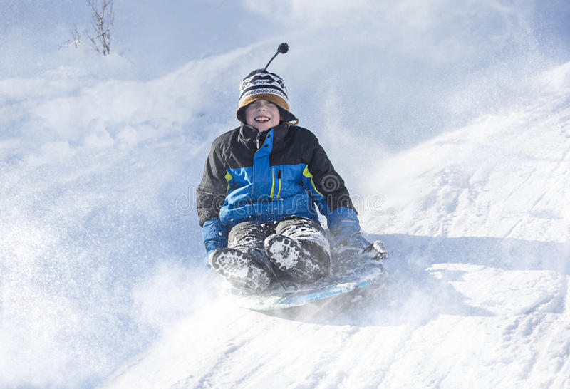 Menino feliz e entusiasmado que Sledding para baixo em um dia nevado imagens de stock