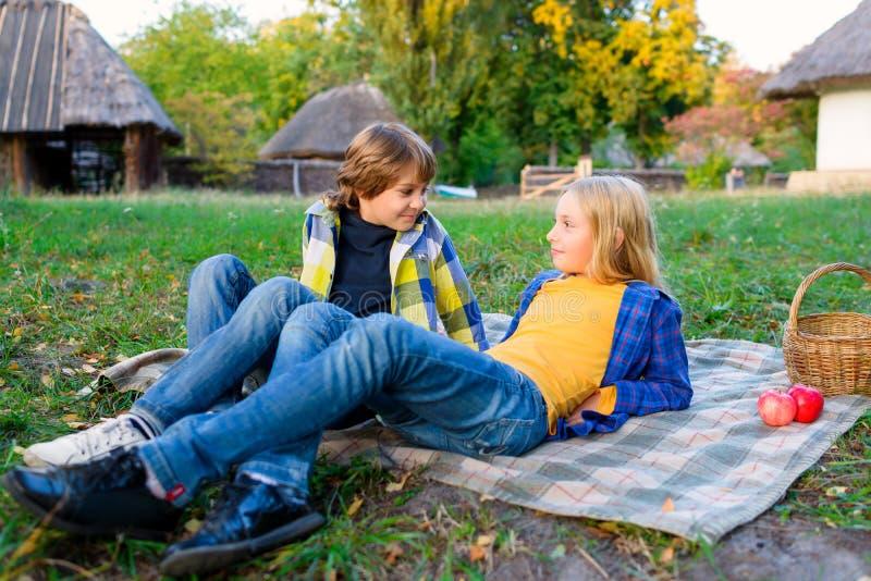 Menino feliz e menina de sorriso que encontram-se junto no tapete foto de stock