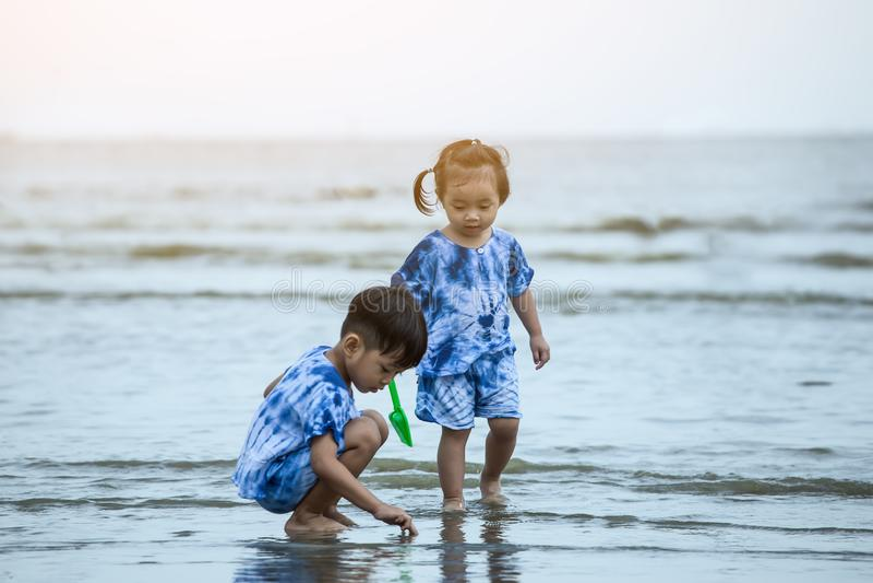 Menino feliz e menina que jogam na praia foto de stock