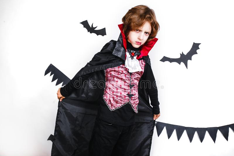 Menino feliz em um traje do vampiro que tem o divertimento fotografia de stock