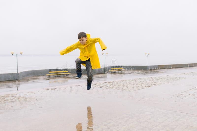 Menino feliz em uma capa de chuva amarela que salta em uma poça fotos de stock