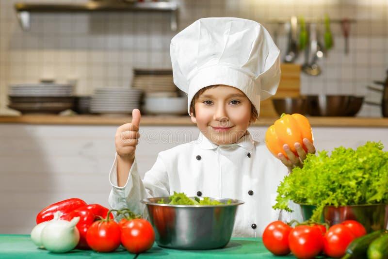 Menino feliz engraçado do cozinheiro chefe que guarda a pimenta de sino ou fotos de stock royalty free