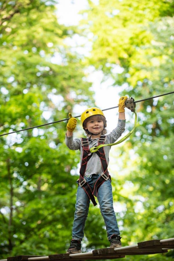 Menino feliz ligando enquanto subia alto em árvores e cordas Toddler subindo em uma estrutura de playground de corda Criança imagem de stock royalty free