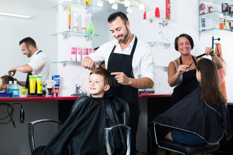 Menino feliz na idade escolar elementar que obtém o penteado do homem foto de stock royalty free