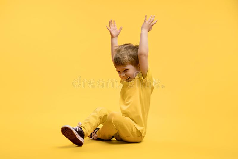 Menino feliz na roupa amarela que sentam-se e nas mãos de aumentação acima fotografia de stock