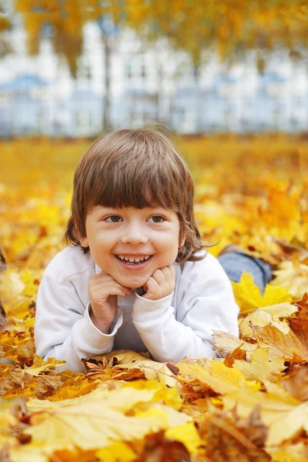 Menino feliz nas folhas do outono fotografia de stock