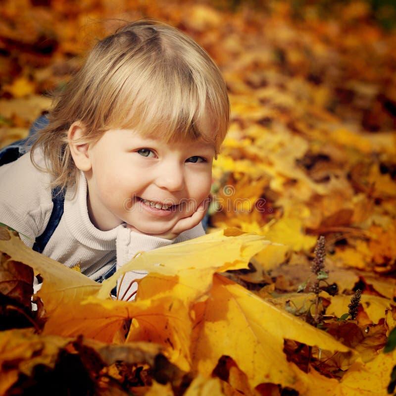 Menino feliz nas folhas do outono fotos de stock