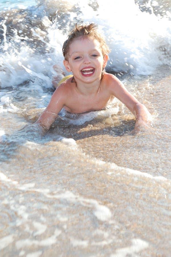 Menino feliz nas ondas foto de stock royalty free