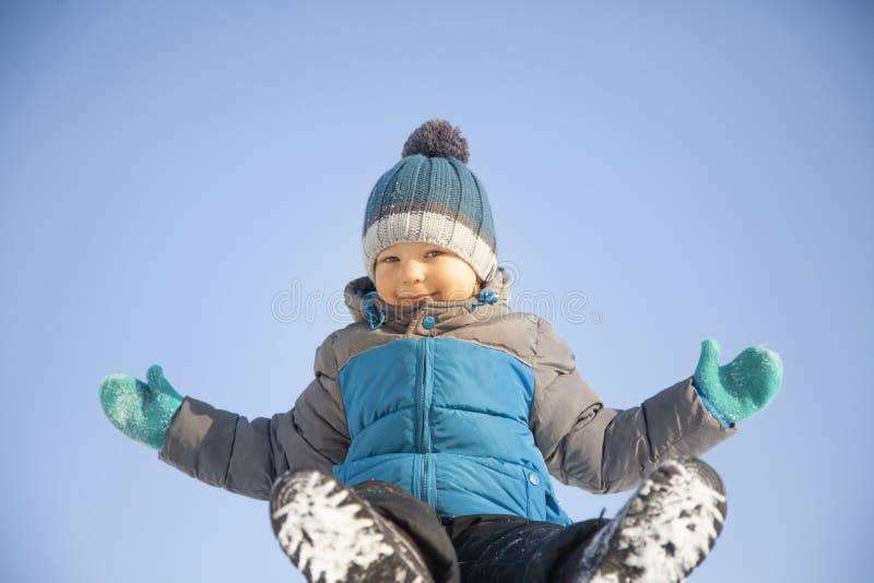Menino feliz no jogo da neve e no dia ensolarado do sorriso fora fotos de stock