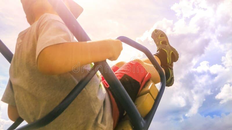 Menino feliz no t-shirt, no short, no boné de beisebol e nas sandálias no balanço do metal com pés acima no céu nebuloso brilhant fotos de stock