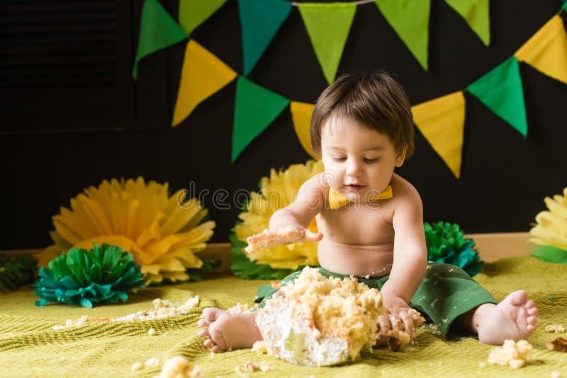 Menino feliz pequeno no primeiro partido do bolo do esmagamento do aniversário imagens de stock