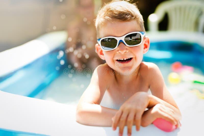 Menino feliz que aprecia horas de verão na piscina imagens de stock