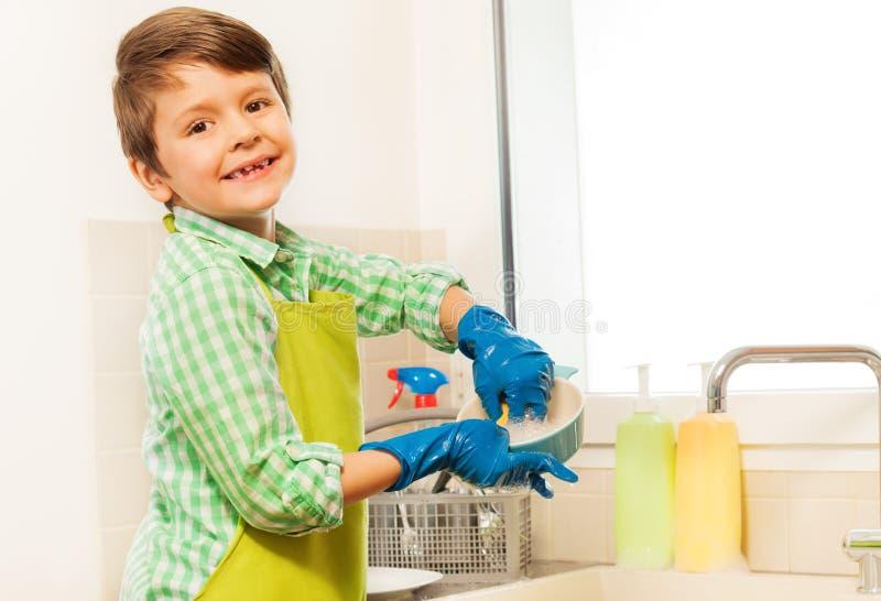Menino feliz que aprende lavar pratos na cozinha foto de stock royalty free