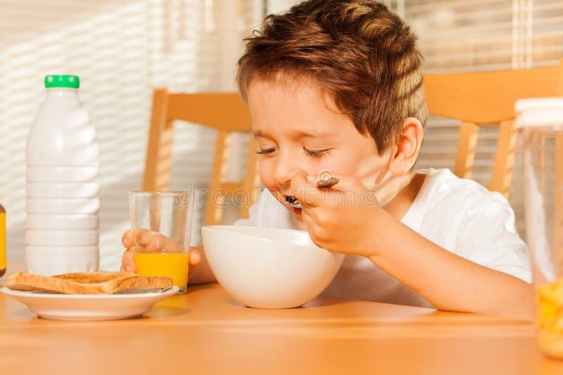 Menino feliz que come cereais e que bebe o suco fresco imagens de stock