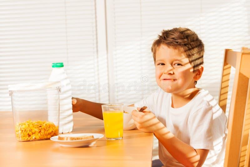 Menino feliz que come flocos de milho na manhã ensolarada fotos de stock royalty free