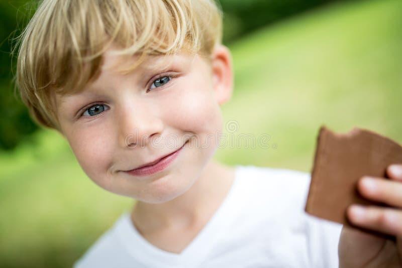 Menino feliz que come o chocolate fotografia de stock royalty free