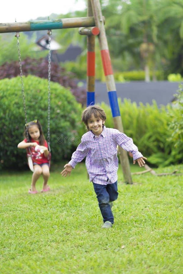 Menino feliz que corre no parque fotografia de stock