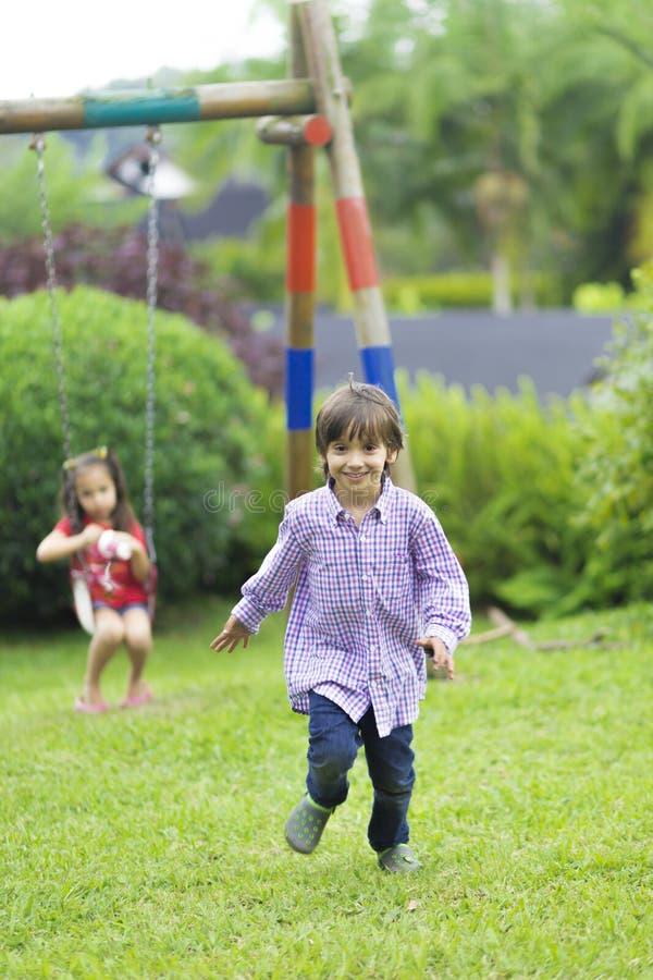 Menino feliz que corre no parque fotografia de stock royalty free