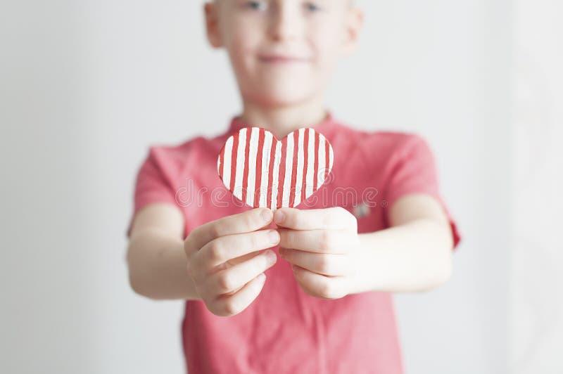 Menino feliz que dá a forma descascada vermelha do coração fotografia de stock royalty free