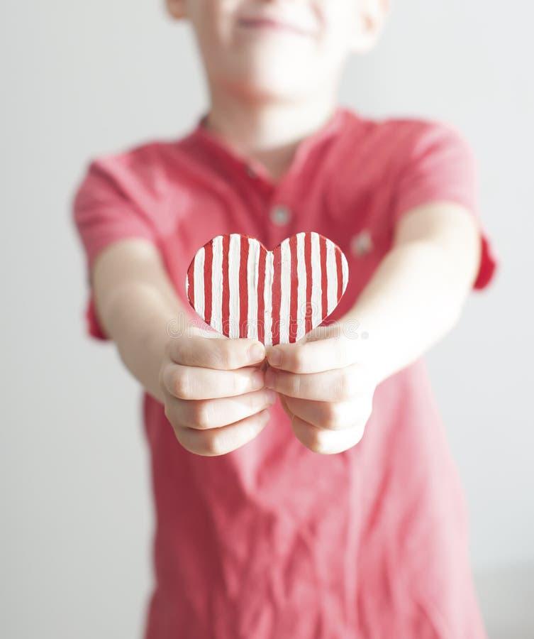 Menino feliz que dá a forma descascada vermelha do coração foto de stock royalty free