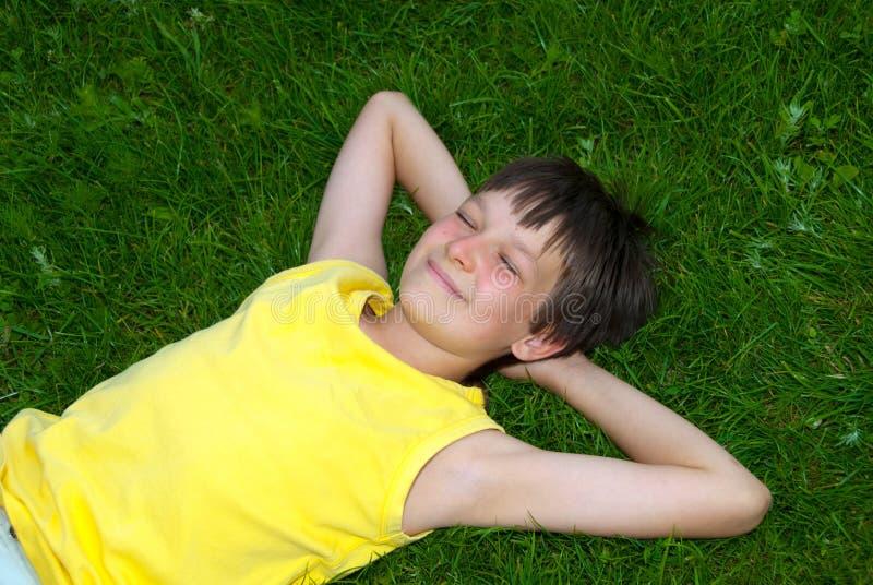 Menino feliz que descansa na grama imagem de stock