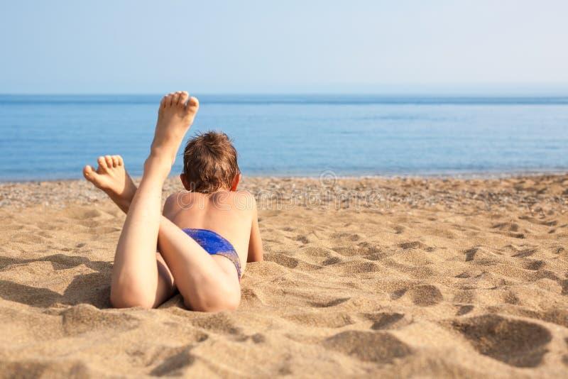 Menino feliz que encontra-se na praia imagens de stock