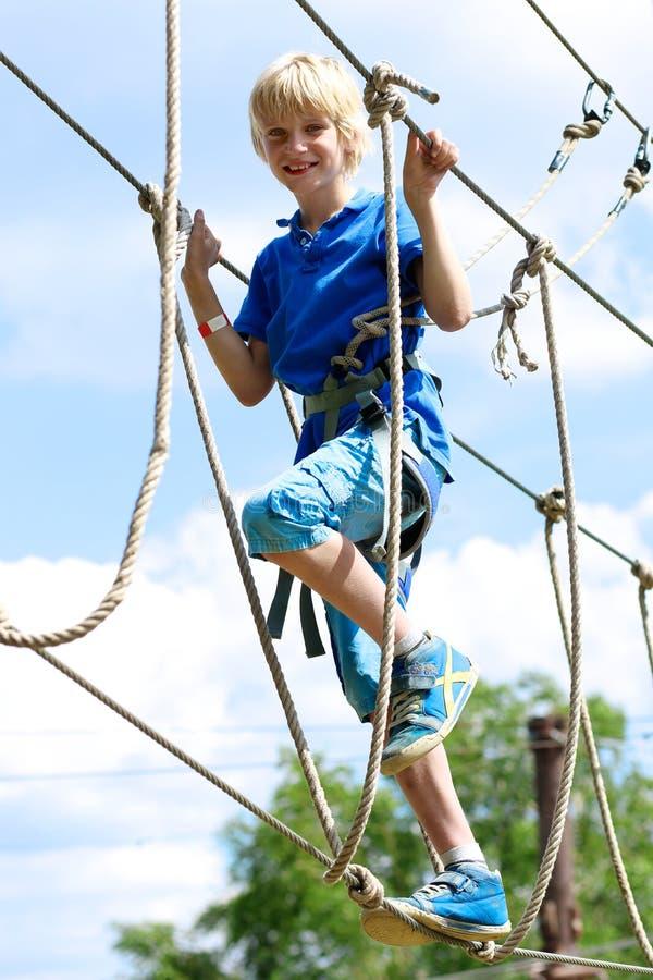Menino feliz que escala no parque da aventura foto de stock royalty free