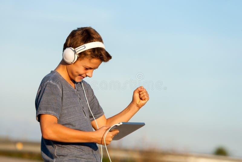 Menino feliz que escuta a música na tabuleta digital. fotografia de stock royalty free