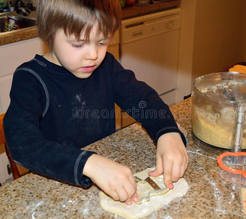 Menino feliz que faz cookies do boneco de neve fotografia de stock royalty free