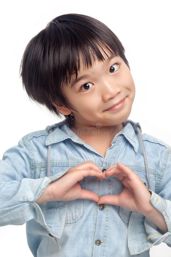 Menino feliz que faz a mão do coração imagens de stock royalty free