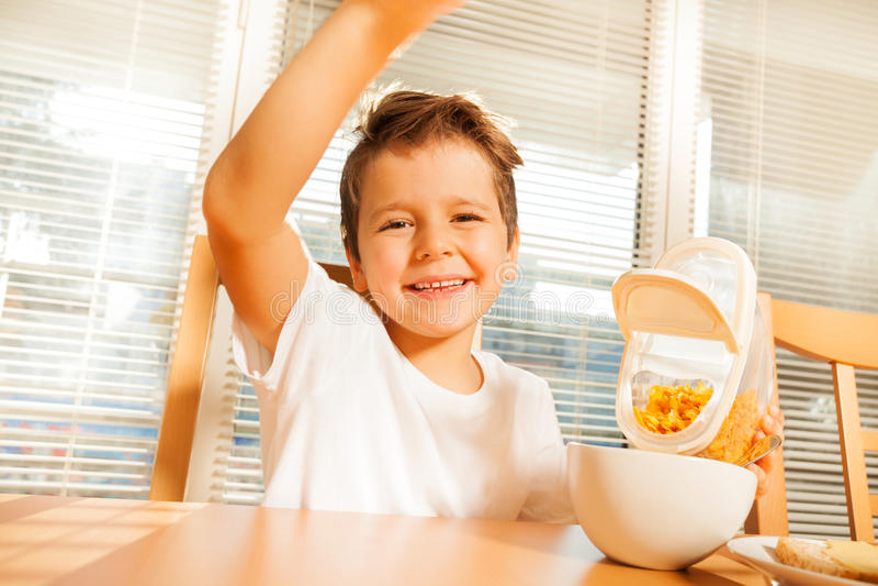 Menino feliz que faz o café da manhã na cozinha imagens de stock