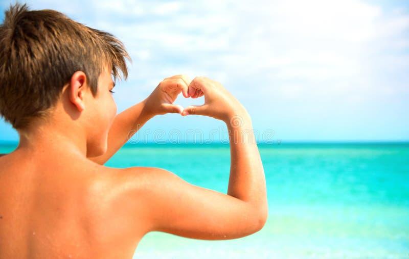 Menino feliz que faz o coração com suas mãos sobre o fundo do mar fotografia de stock