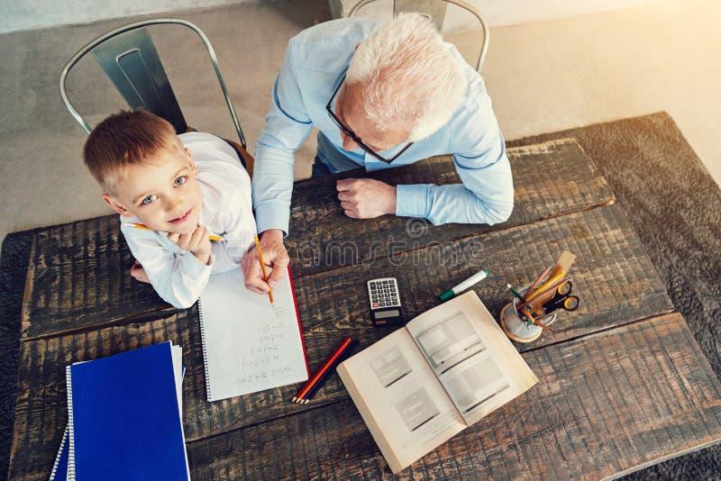 Menino feliz que faz trabalhos de casa com seu vovô inteligente imagem de stock