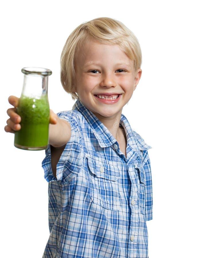 Menino feliz que guarda a garrafa do batido verde fotografia de stock