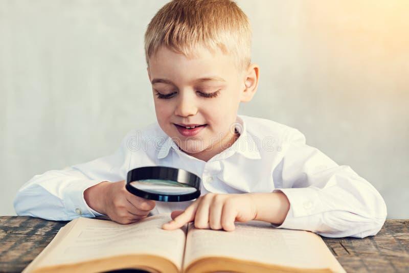 Menino feliz que guarda uma lupa ao ler foto de stock