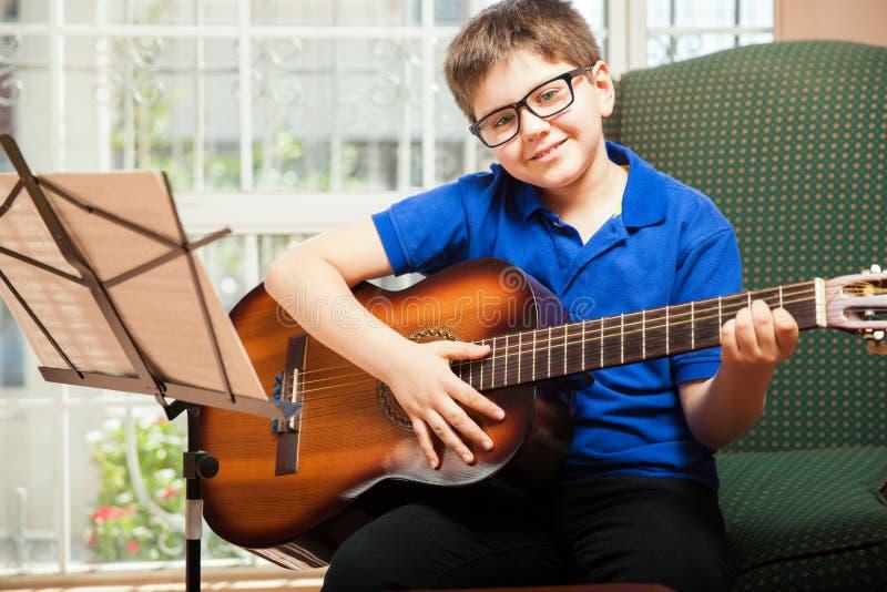 Menino feliz que joga a guitarra foto de stock