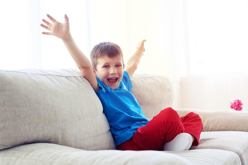 Menino feliz que levanta as mãos ao sentar-se no sofá imagem de stock